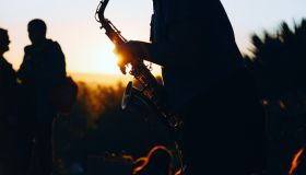 Midsection Of Silhouette Man Playing Saxophone Against Clear Sky During Sunset
